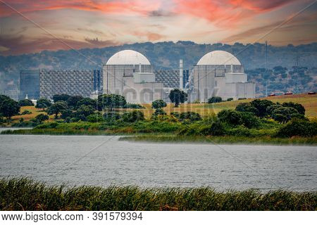 Spanish nuclear power plant next to a river with a stunning sky on the background