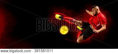 Soccer player in action on dark smoke background. Sports banner. Copy space background