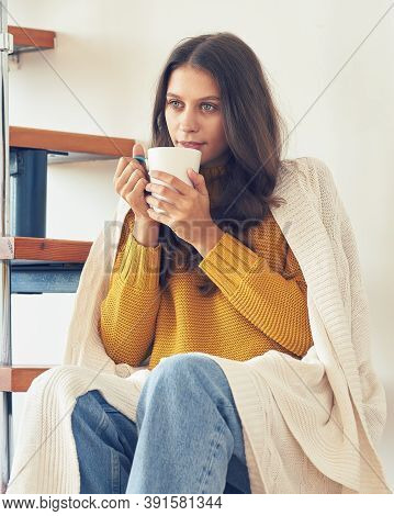 Bautiful Young Woman Sitting Onstairs In Warm Clothes And Drinking Coffee, Wrapped In Blanket