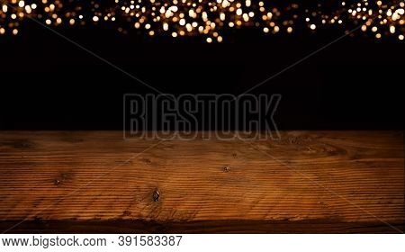 Celebration Background With Festive Golden Bokeh Lights And Rustic Wooden Table. Chistmas And New Ye