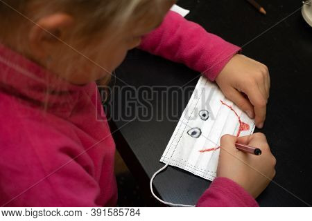 Little Girl Paints A Medical Mask. Draws A Smile On It And Eyes - A Smiley. Pandemic