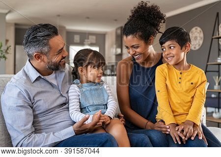 Happy latin family sitting on sofa and laughing together. Middle eastern parents playing with daughter and son at home. Indian father sitting with daughter while african mother and brother smiling.