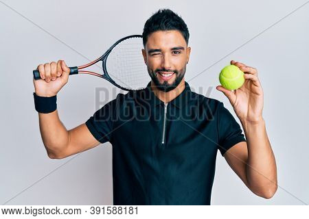 Young man with beard playing tennis holding racket and ball winking looking at the camera with sexy expression, cheerful and happy face.