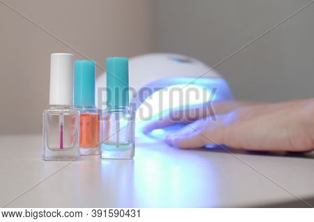 Three Colorless Transparent Nail Polish Bottles In Background Of Female Hands In Gel Uv Led Nail Whi