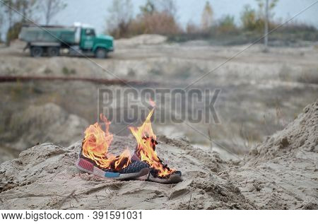 Burning Sports Sneakers Or Gym Shoes On Fire Stand On Sandy Beach Coast. Athlete Burned Out. Physica