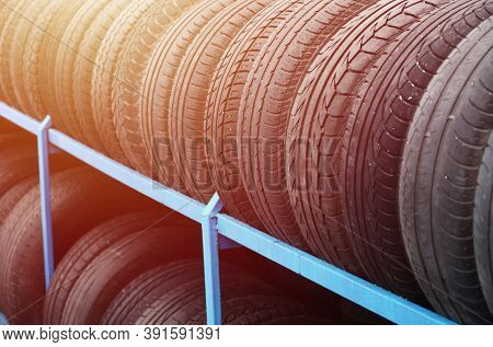 Rack With Variety Of Car Tires In Automobile Store. Many Black Tires. Tire Stack Background