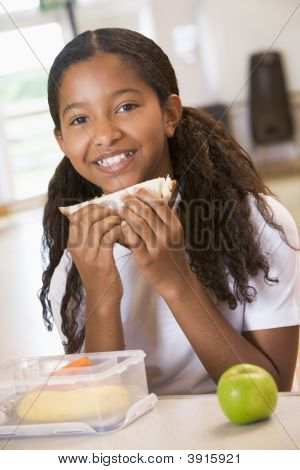 Student in cafeteria eating lunch (selective focus) poster