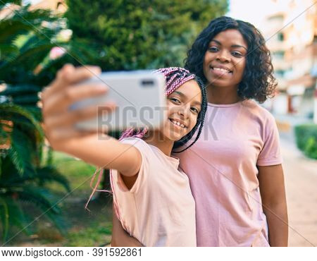 African american mother and daugther hugging and making selfie by the smartphone at the park.