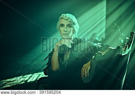 A beautiful old woman, a noble widow with gray hair and a rich black dress, sits on a vintage sofa in her old castle in the rays of light. Black widow. Fantasy world. Halloween.