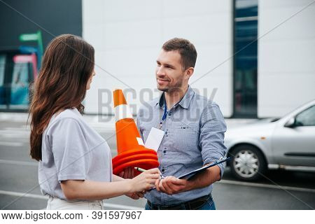 Female Student Helps To Pack Traffic Cones, Male Driving Instructor Smiles With Gratitude. Young Wom