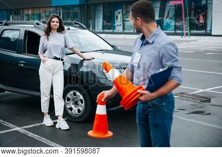 Female Student Waiting For The Driving Instructor To Finish Collecting Traffic Cones, Standing And P