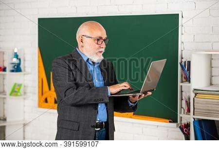 Videoconferencing Keeps Homebound Students Connected. Senior Intelligent Man Teacher Use Laptop. Dis