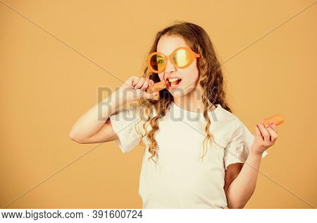 Girl Eat Carrot Vegetable And Drink Carrot Juice. Vitamin Nutrition. Fashion Kid Sunglasses Drink Re