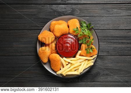 Tasty Fried Chicken Nuggets With Garnish On Wooden Table, Top View