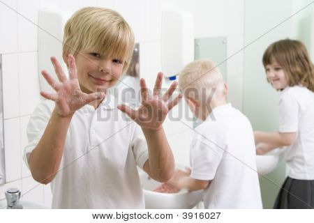 Students in bathroom at sinks washing hands with one holding up soapy hands (selective focus) poster