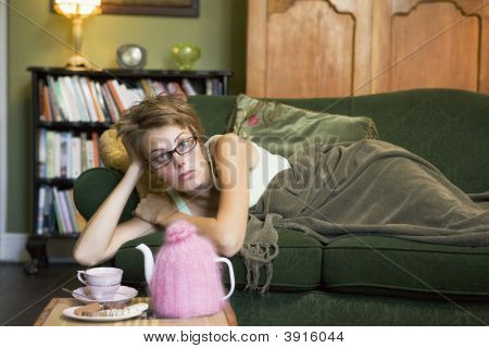 Woman Sat On Sofa Looking At Camera With Tea Set On Table