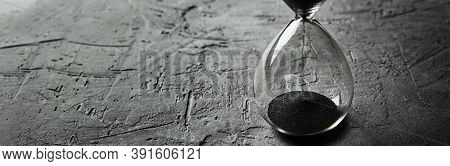 Hourglass On Dark Background, Long Banner. Urgency And Running Out Of Time Concept