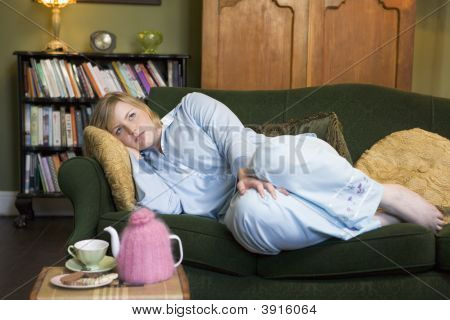 Woman Laid On Sofa With Biscuits And Tea On Table