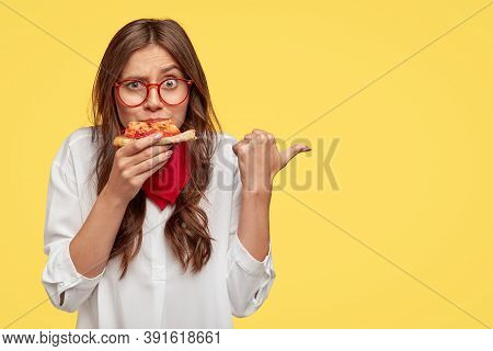 Horizontal Shot Of Surprised Female Eats Tasty Slice Of Pizza, Dressed In Fashionable Clothes, Indic