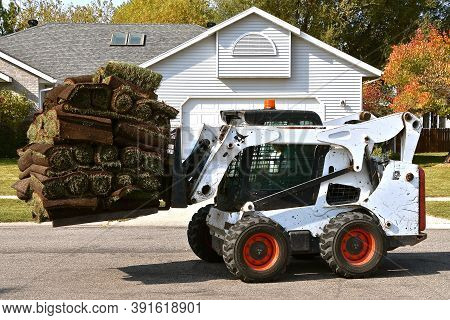 Moorhead, Minnesota, March 9, 2019: The Bobcat Skid Steer Moving A Loaded Pallet Of Rolled Sod Is He