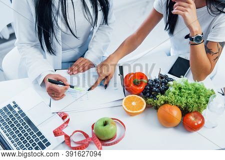 Top View Of Female Nutritionist That Gives Consultation To Patient Indoors In The Office.