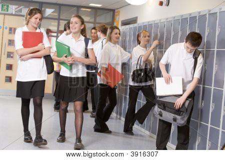 Teens In School Corridor On Way To Class