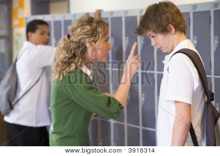 Teen Boy Being Told Off By Teacher In School Corridor