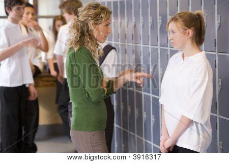 Teen Girl Being Told Off By Teacher In School Corridor