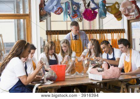 Teacher Helping Teen Pupils In Art Lesson