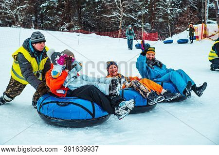 Lviv, Ukraine - January 7, 2019: Family Ride Down By Snowing Hill With Snow Tube