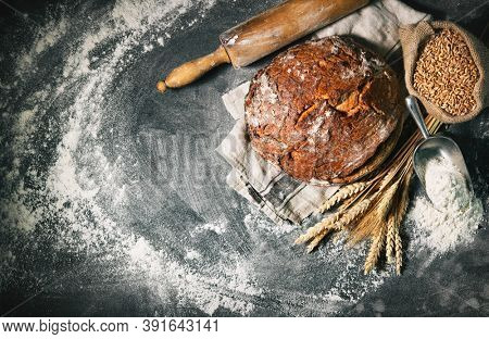 Freshly baked traditional loaf of bread on rustic table decorated with flour and grain