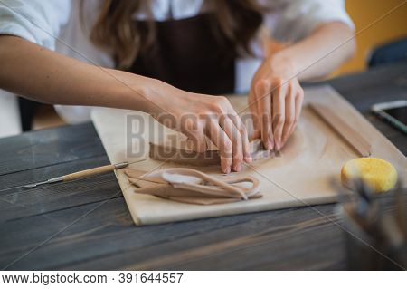 Close Up Of Skilled Craftswoman Removing Part Of Clay While Making Ceramic Product In Pottery Worksh