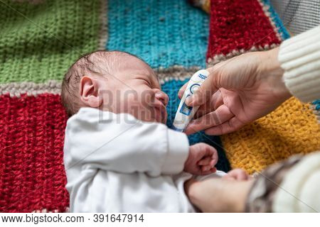 Unwell Newborn Baby Lying On Crocket Knitted Bed Crying While Selective Focus Of Hands Of Young Fema