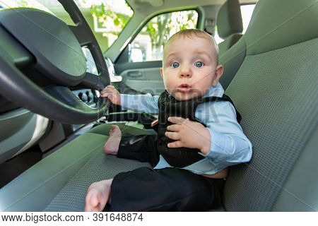 Portrait Of Excited And Curious Infant Baby Boy In Formal Clothing Sitting On Drivers Seat Holding S