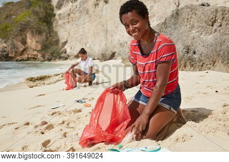 Positive Ethnic Woman With Happy Smile, Carries Garbage Bag, Picks Up Litter, Poses On Knees, Tidies
