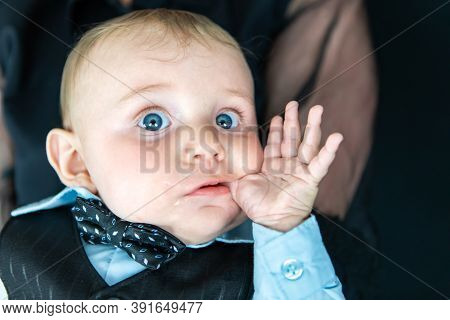 Portrait Of Cute Little New Born Baby Boy Dressed In Formal Clothes With Bow Sucking Finger In Mouth