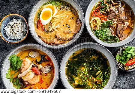 Assorted Traditional Asian Soups. Miso, Ramen, Tom Yam, Pho Bo. Black Background. Top View