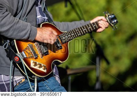 Selective Focus Of Young Male Guitarist Playing Electric Musical Instrument During Cultural Fiesta W