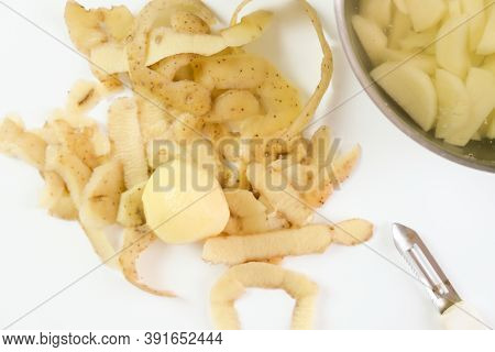 Peels And Peeled And Cut Potato On A White Table, Cookinf Vegetable Dishes Concept