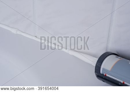 Plumber Applying Silicone Sealant To The Tile Joint