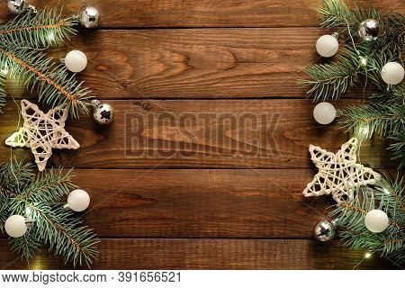 Wooden Christmas Background With Pine Tree Branches Decorated Gold Christmas Lights, Stars, Baubles.