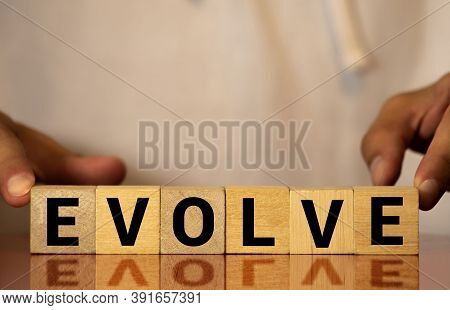 Evolve Word Written On Wood Block. Evolve Text On Wooden Table For Your Desing, Concept.