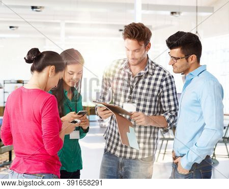 Office meeting. Young business people meeting in office using phone working with tablet.