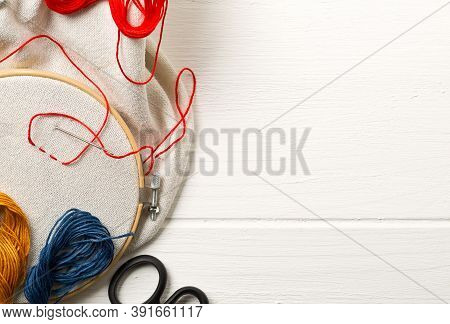 Round Stitching Or Embroidery Frame With Red Stitching And Sewing Tools On White Wooden Background,