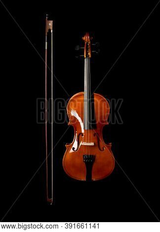 Brown Wooden Fiddle Or Violin, Classic Musical Instrument, With Bow Next To It Isolated Over Black B