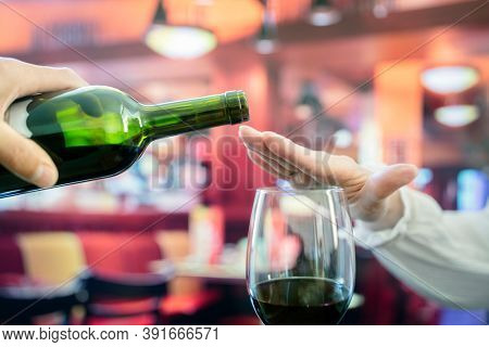 Womans hand rejecting more alcohol from wine bottle in bar concept for alcoholism or drunk driving