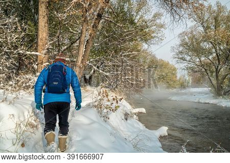 senior male is hiking along the Poudre River in Fort Collins, Colorado - foggy fall scenery with a fresh snow