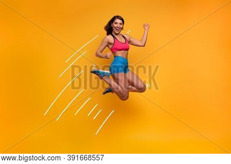 Sport Woman Jumps On A Yellow Background. Happy And Joyful Expression.