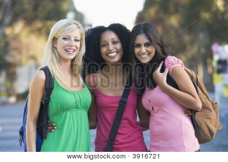 Three women outdoors standing with arms around each other (selective focus) poster