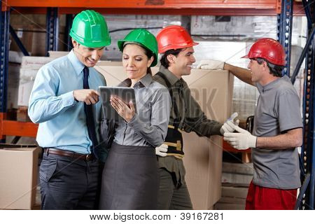 Supervisors using digital tablet and foremen discussing work at warehouse